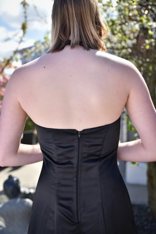 Stort åbent rygstykke. Faconsyet kjole, der fremhæver talje og falder meget smukt