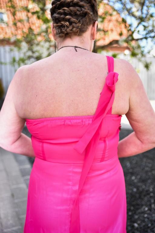 Slør bindes bagtil over den enes kulder. Elastik i kant der sikrer at kjolen sidder til.